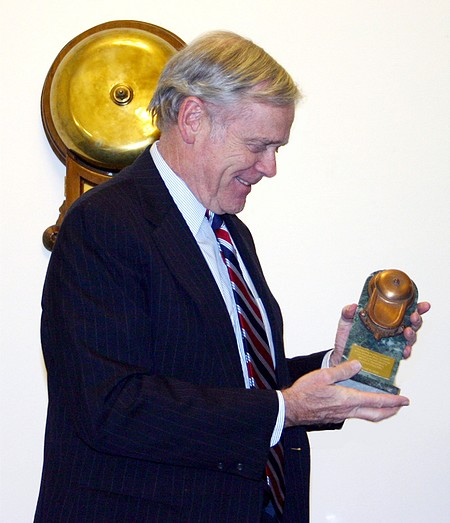 W. H. Donaldson with replica of BSE bell with actual BSE bell in the background